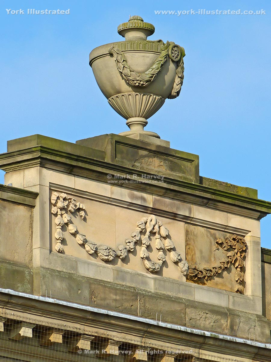 Photograph: Garlanded urn on pedestal above front facade of Assize Courts Building, York.
