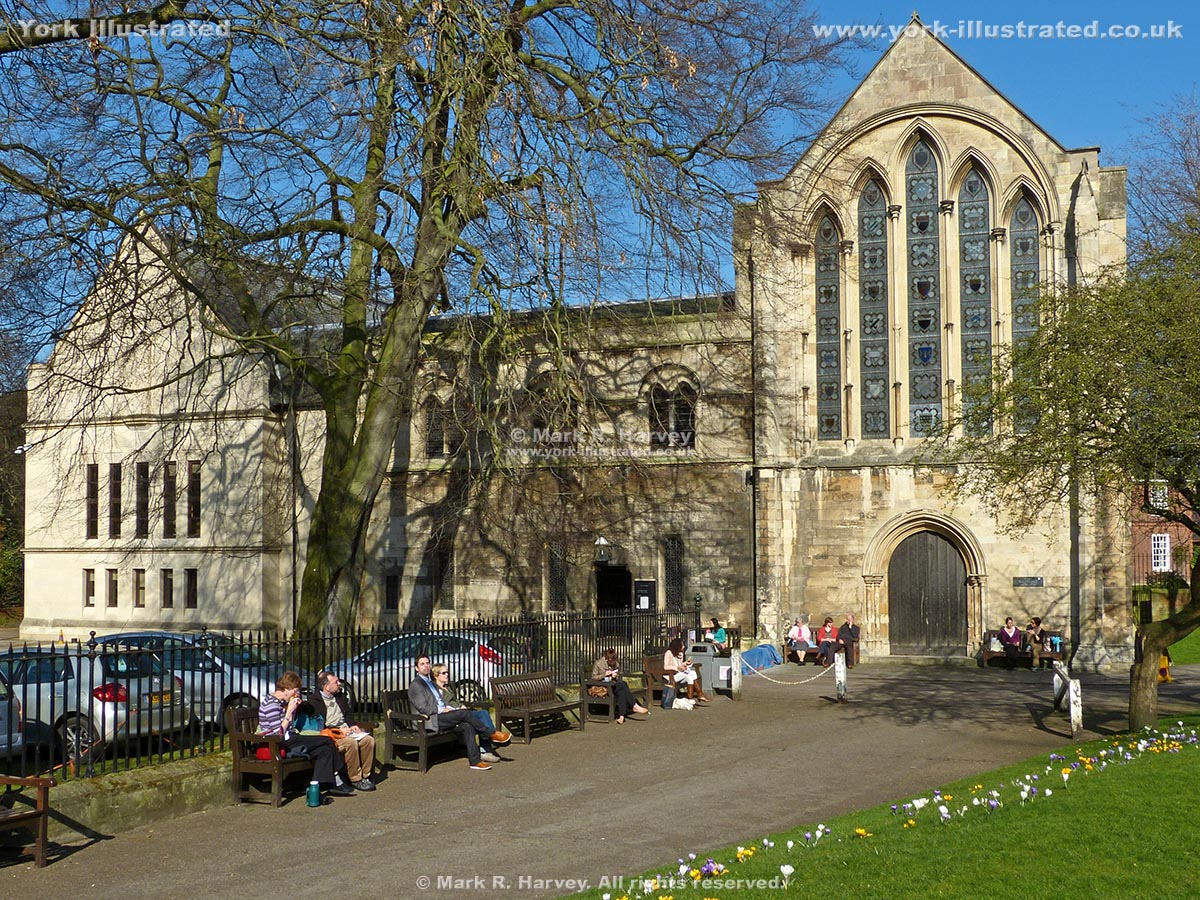 Photo: The Minster Library (York), with crocuses and people sitting on bench seats in Dean's Park in the foreground.