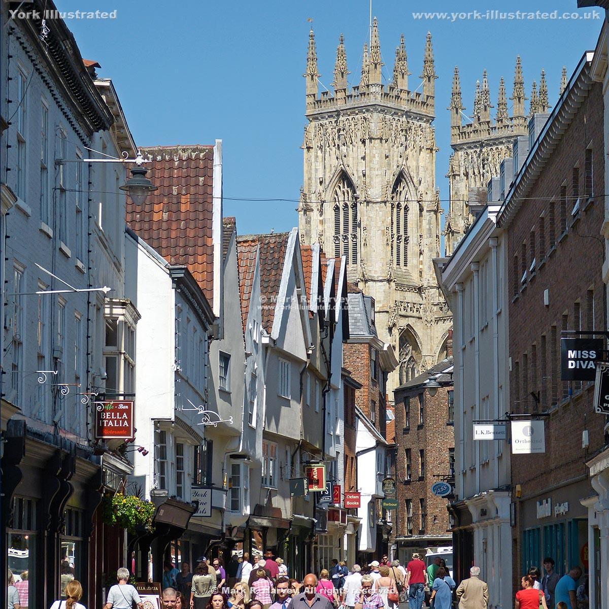 Photograph: Low Petergate (York), with the bell towers of the Minster beyond.