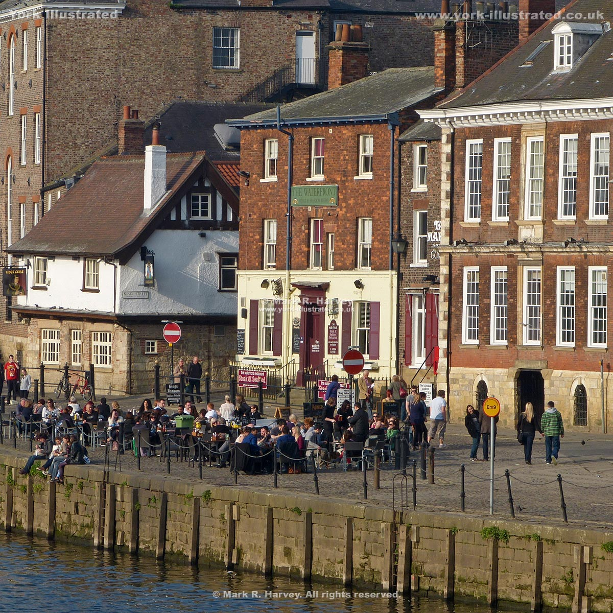 Photograph: The River Ouse, Cumberland House and people relaxing on King's Staith (York).