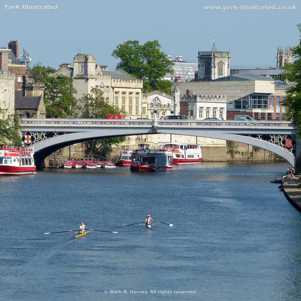 Photograph: Two single sculls and tour boats on River Ouse (York) plus Lendal Bridge.