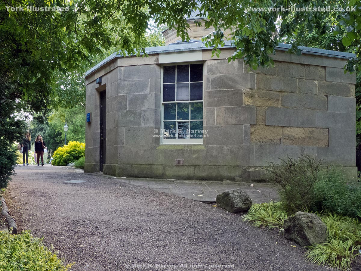 Photograph: Plants frame the path beside the York Observatory (Museum Gardens).
