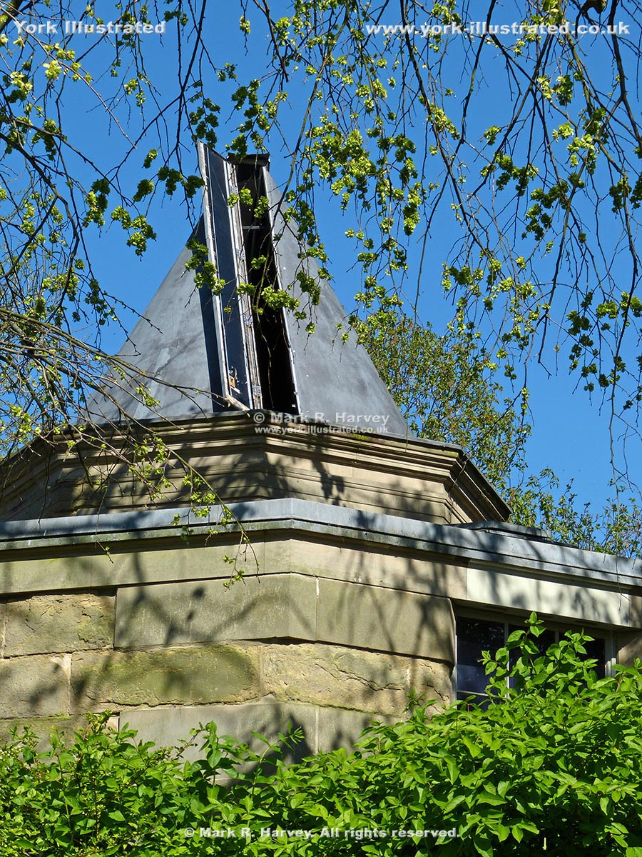 Photograph: Roof and open viewing slot of York Observatory, surrounded by shrubs and trees.